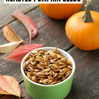Roasted Pumpkin Seeds with powdered chipotle and small pumpkins in background with leaves
