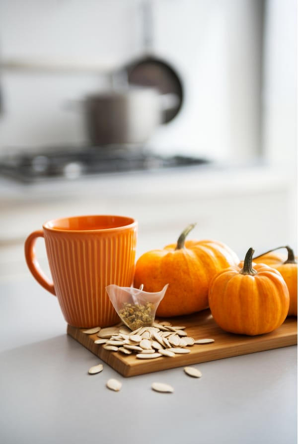 mini pumpkins, pumpkin seeds and orange mug on kitchen counter