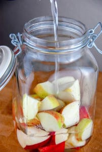 apples in jar with pouring vodka for homemade apple-infused vodka