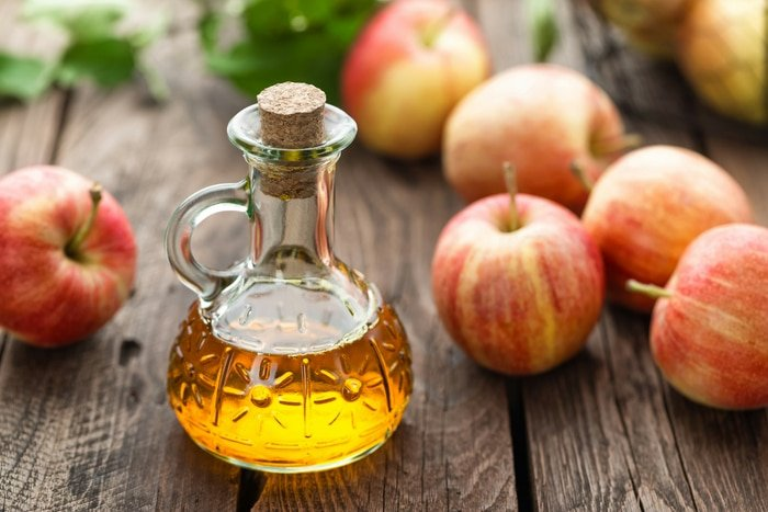 Apple cider vinegar in carafe with apples