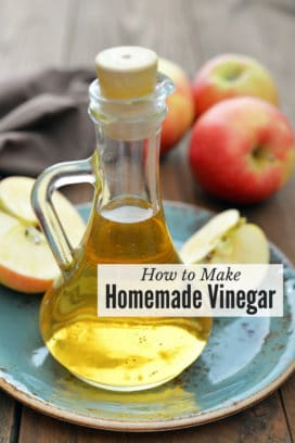 Carafe of apple cider vinegar with apples (titled image of how to make homemade vinegar)
