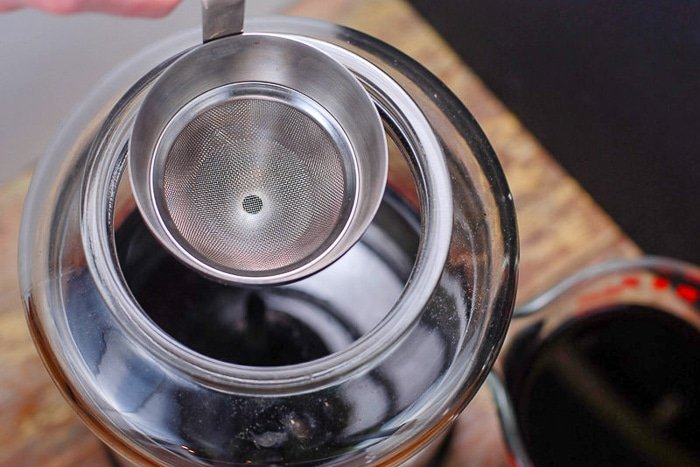 Using a funnel to add red wine to homemade vinegar batch