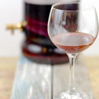 Wine goblet of homemade red wine vinegar with vinegar making glass jar in the background