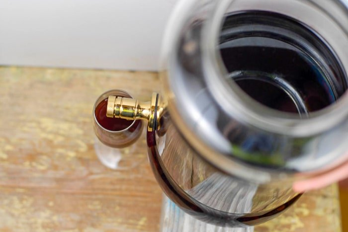 Homemade red wine vinegar drained into a wine glass with spigot