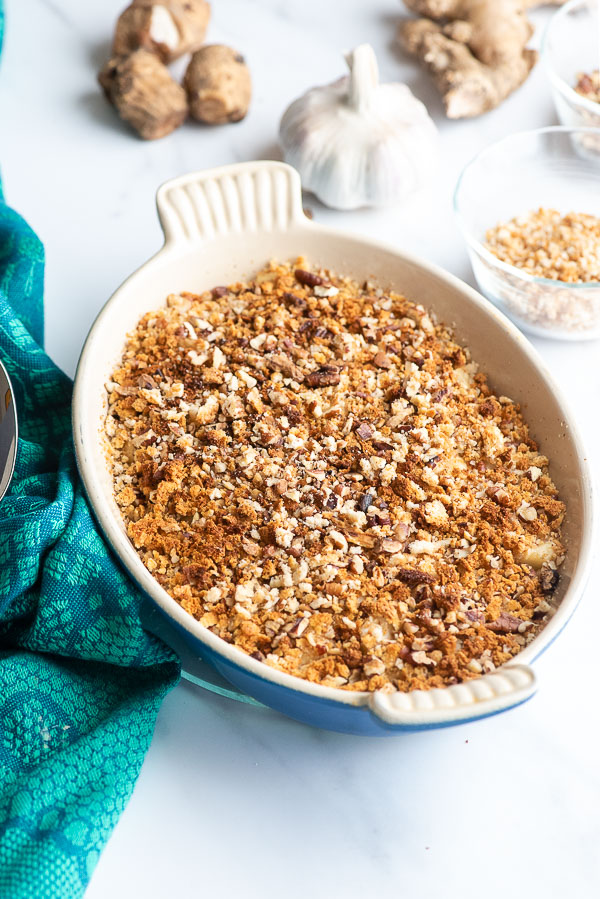 Scalloped Sunchokes with crunchy nut and breadcrumb topping in pan