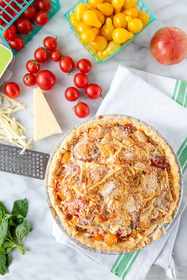 Fresh from oven Savory Tomato Pie recipe with cherry tomatoes, cheese and white kitchen towel