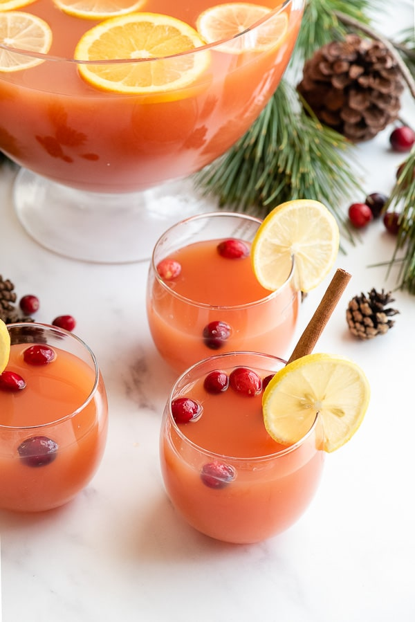 Glasses of warm Wassail with cranberries and lemon slices