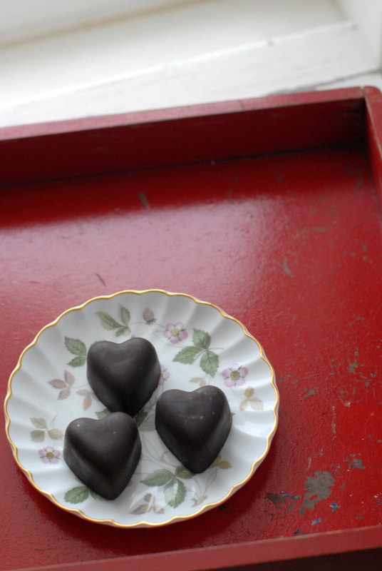 three chocolate hearts on floral china plate