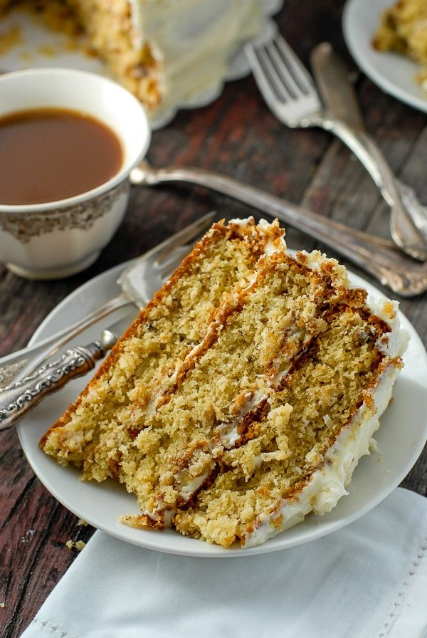 large slice of Italian Cream Cake with a cup of coffee in the background
