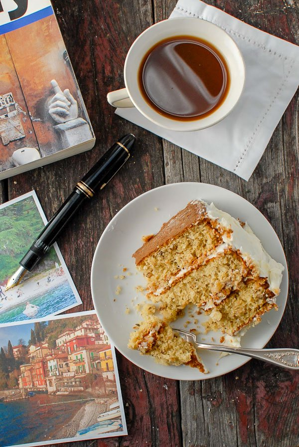 Partial slice of Italian Cream Cake with cup of coffee and travel book