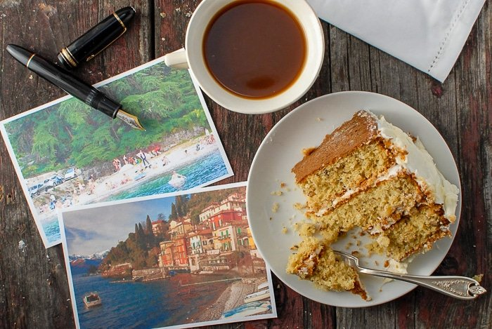 slice of Italian Cream Cake with post cards and a fountain pen