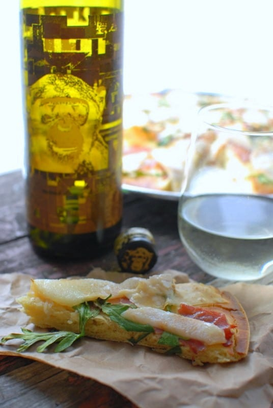 unbaked slice Pear Proscuitto Arugula Pizza slice with wine bottle