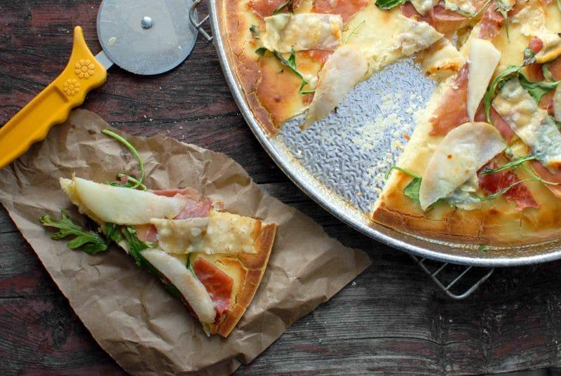 slice Pear Proscuitto Arugula Pizza and pizza cutter
