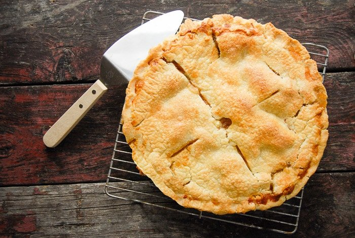 Pear pie on cooling rack with pie cutter