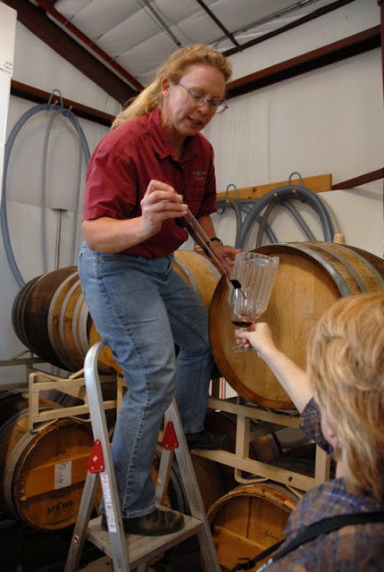 A person extracting wine from a barrel in Grand Valley