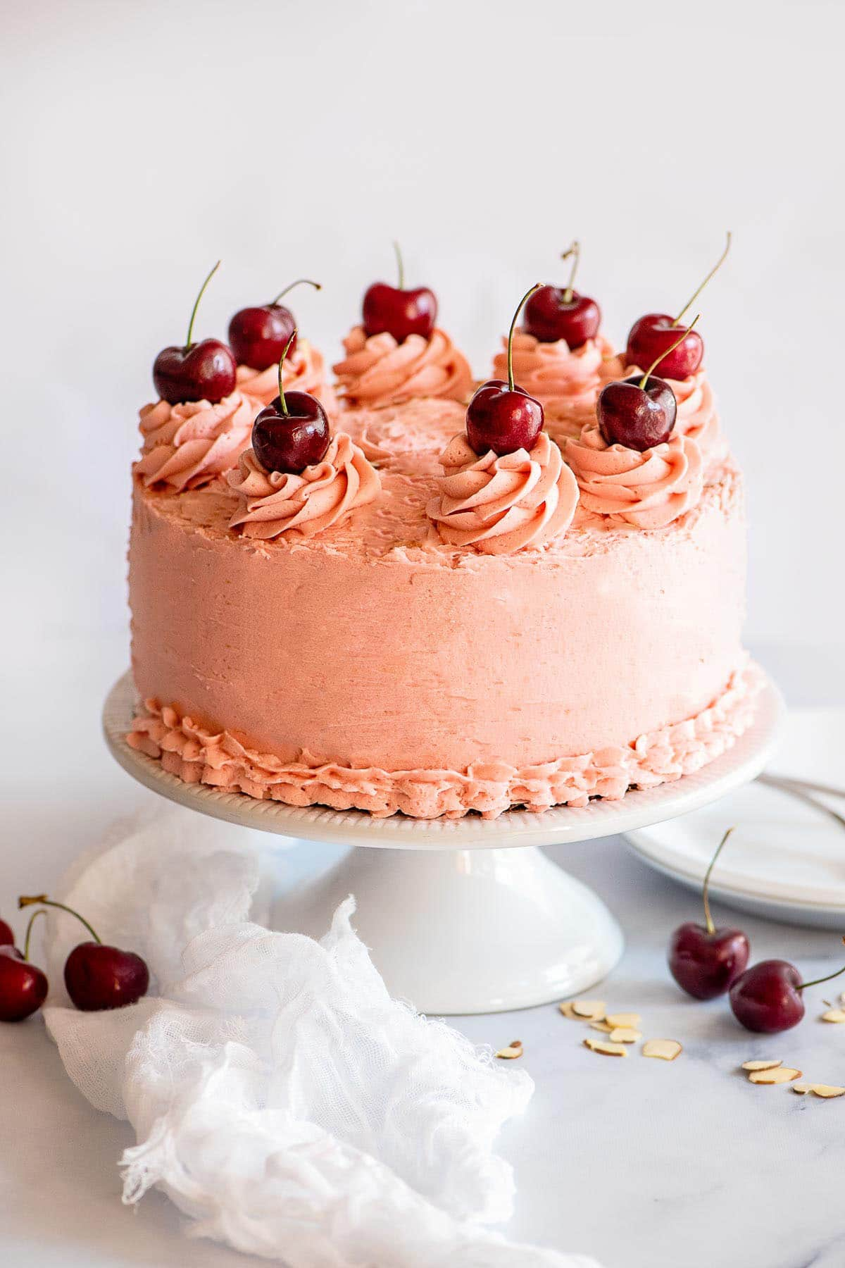 cherry sour cream cake on pedestal