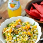 Freshly made spicy and sweet Grilled Peach and Corn Salsa in a white ruffle-edged with red corn tortilla chips, bottled lemonade BoulderLocavore.com