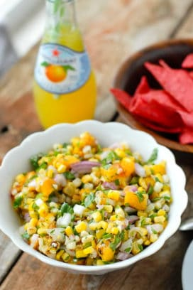Grilled Peach and Corn Salsa in a white ruffle-edged with red corn tortilla chips, bottled lemonade
