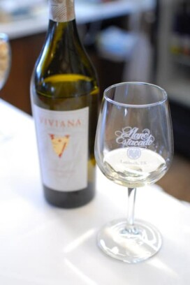 A close up of a bottle and a glass of wine, with Llano Estacado and Texas