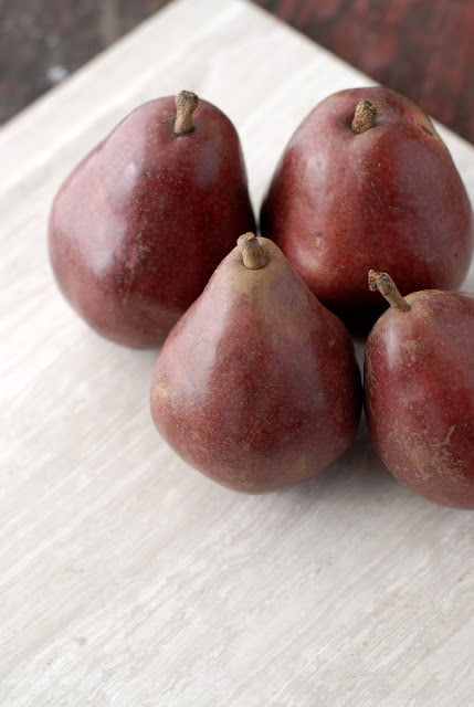 5 red pears on table