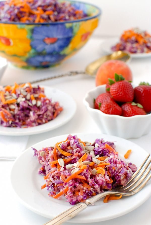 colorful slaw with red cabbage and carrot with peach-strawberry dressing on white plates