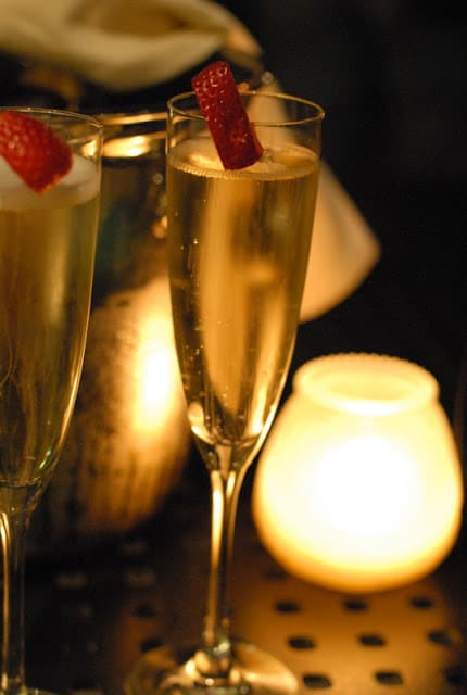 glasses of champagne with strawberry on rim in candlelight