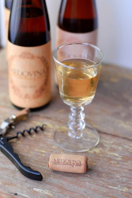 A close up of a bottle and a glass of mead