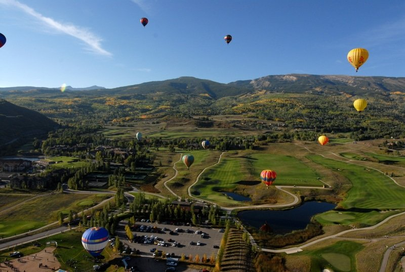 A group of people flying balloons on a grassy hill