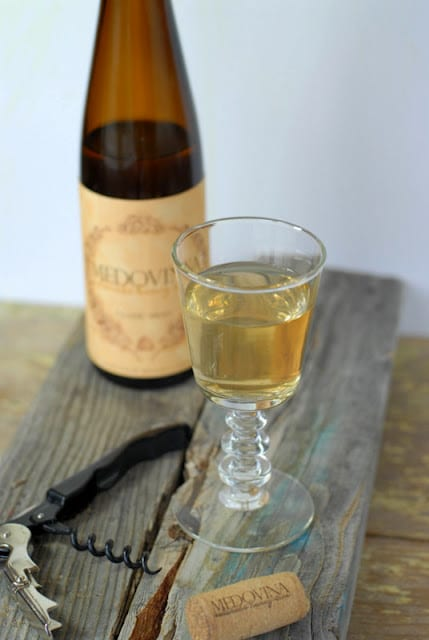 A bottle of mead sitting on top of a wooden table