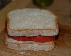 A cut in half sandwich sitting on top of a wooden cutting board, with Toast