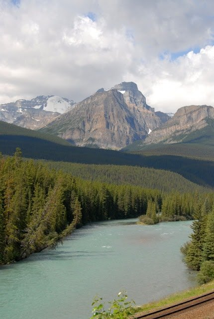 A view of a lake surrounded by trees and a mountain in the background