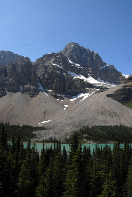 A snow covered mountain with glacier lake in foreground