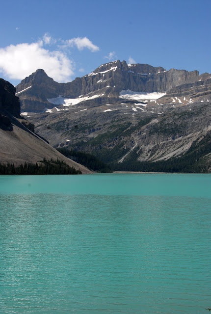 blue glacial lake with snowy mountains in background