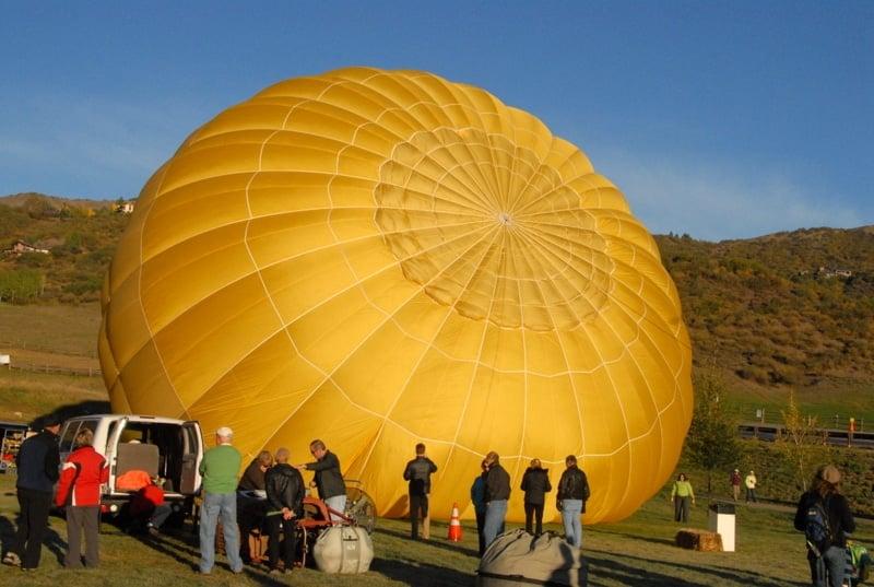 Inflating a yellow hot air balloon