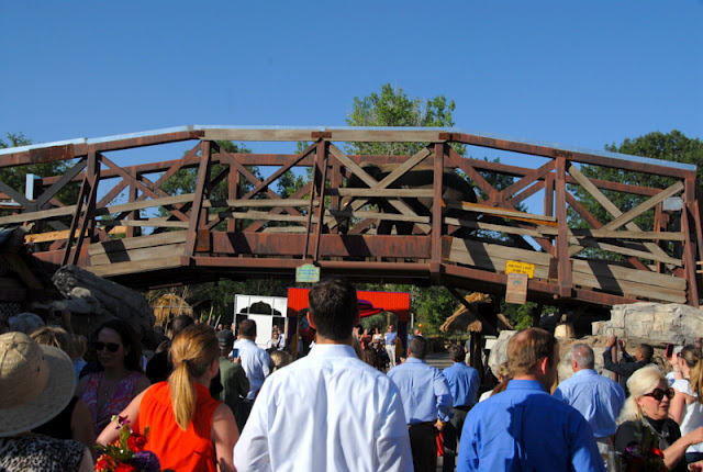 elephant walking over bridge above a crowd