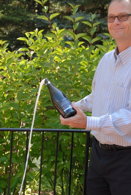 A man holding a spraying champagne bottle