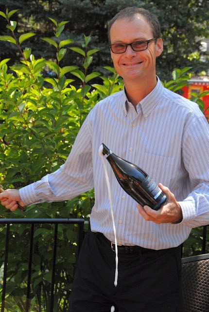 A person standing next to a fence with champagne bottle