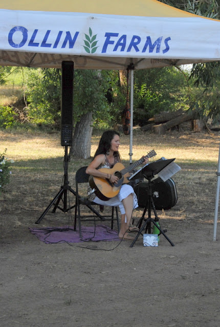 A personplaying guitar at farm dinner