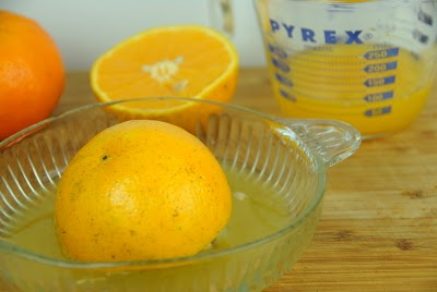 A bowl of oranges on a table, with Lemon and Orange juice