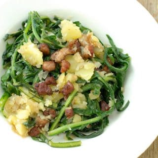 Warm Dandelion and Bacon salad in a white salad bowl