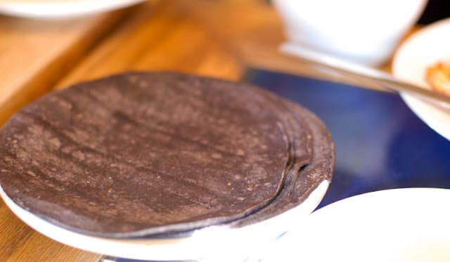 A close up of a plate of food with a fork blue tortillas