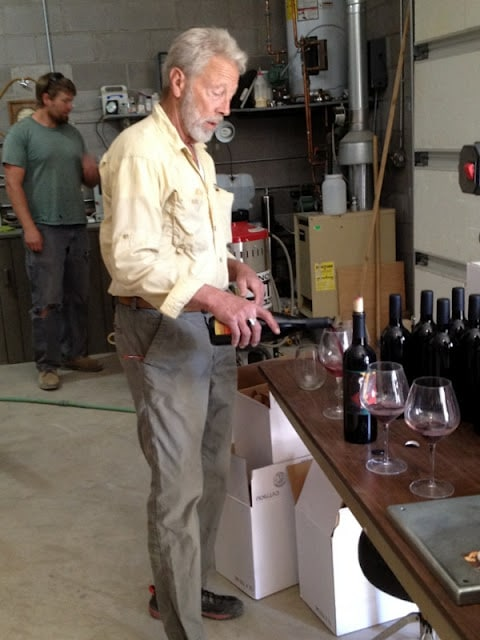 A man standing in a kitchen pouring wine at Alfred Eames Cellars