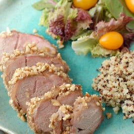 slices of pork tenderloin with peanuts on outside on plate