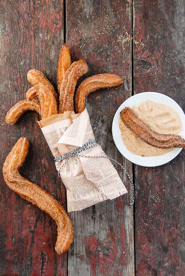 Churros wrapped in newspaper and in cinnamon sugar