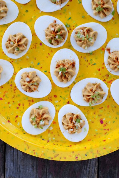 spicy deviled eggs on yellow egg plate