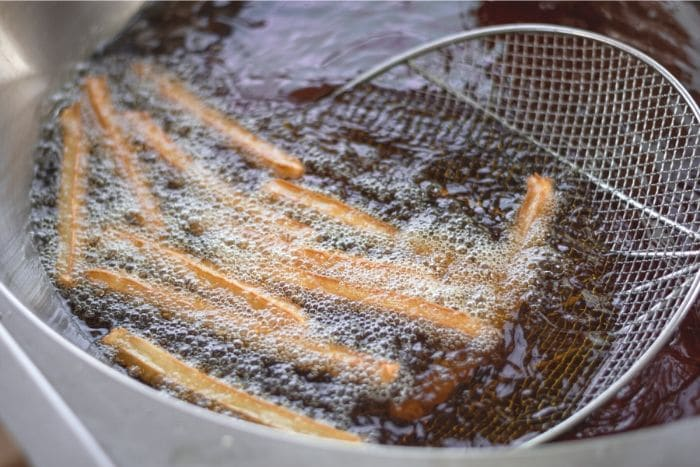 frying churros with strainer scoop