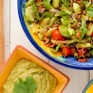 Taco Salad Ole in a colorful large bowl with Avocado Tequila Lime Dressing in a smaller orange bowl
