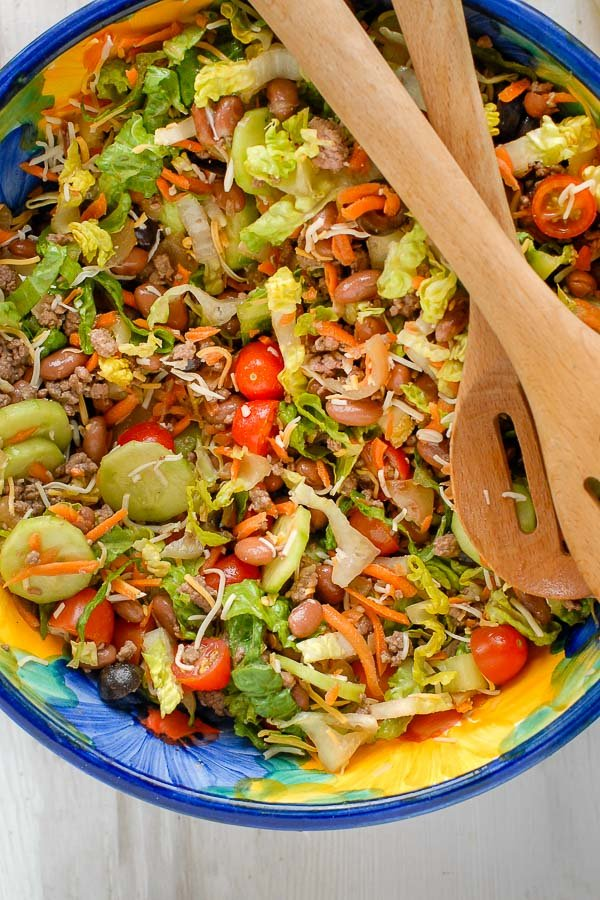 Colorful bowl of Taco Salad Ole with wooden salad servers
