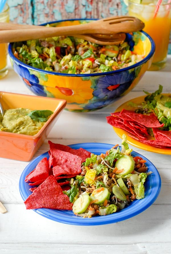 Side salad portion of Taco Salad Ole on blue plate with red tortilla chips and large bowl of salad in the background
