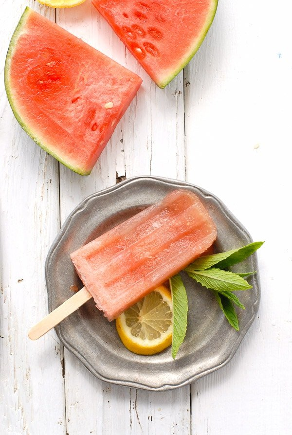 Costa Rican Watermelon Mojito Popsicles and watermelon wedges. A refreshing boozy popsicle recipe inspired by a Costa Rican cocktail. Watermelon, mint and a touch of rum take the edge off any hot day! - BoulderLocavore.com